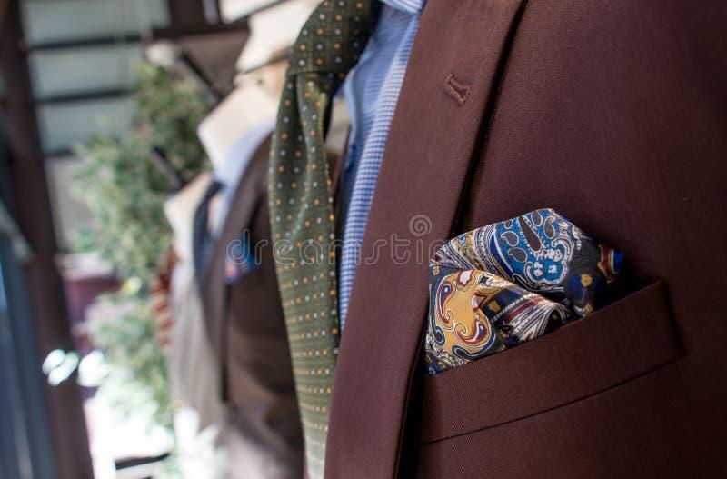 Ventana de la tienda de la tienda para hombre del sastre que muestra el material y las telas brillantemente coloreados su del tra imagenes de archivo