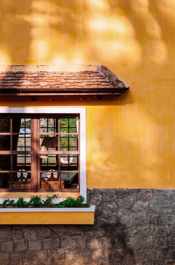 Ventana de madera en la pared amarilla de la casa de campo foto de archivo