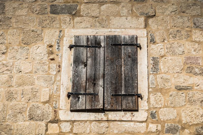 Ventana de madera vieja cerrada en la pared de piedra fotos de archivo libres de regalías