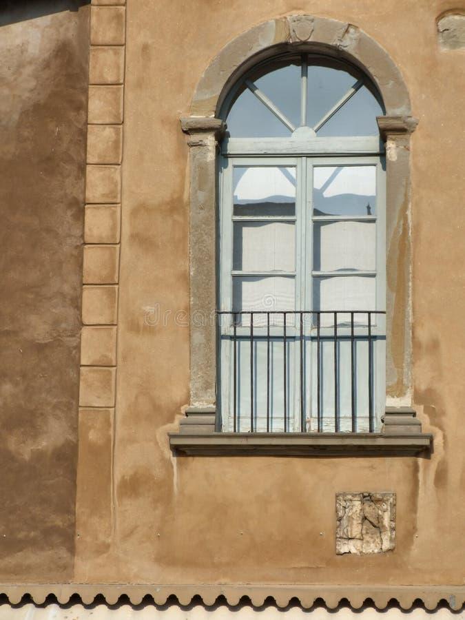 Ventana decorativa en una pared marrón foto de archivo