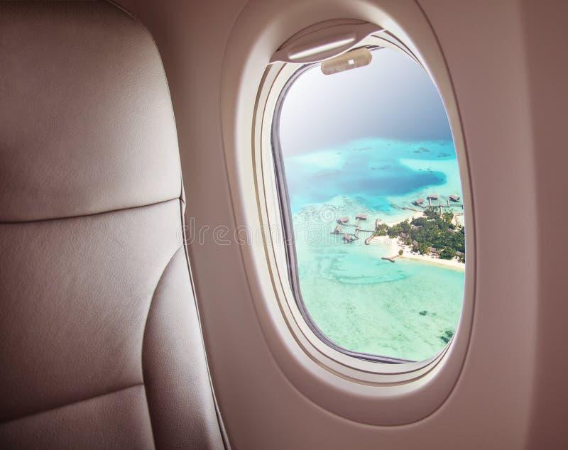 Ventana del aeroplano con la opinión hermosa de la isla de Maldivas imagen de archivo