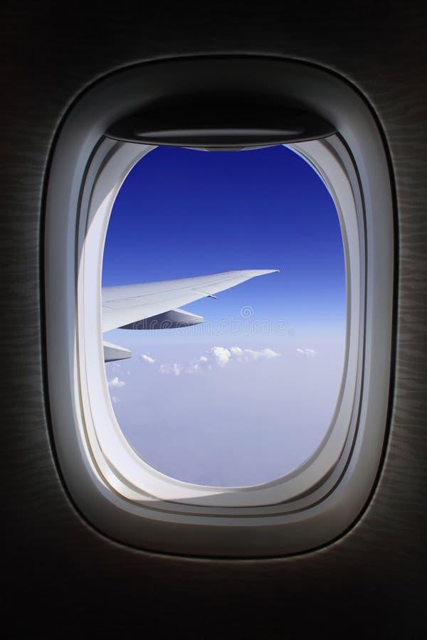 Ventana del avión con los cielos azules fotografía de archivo libre de regalías