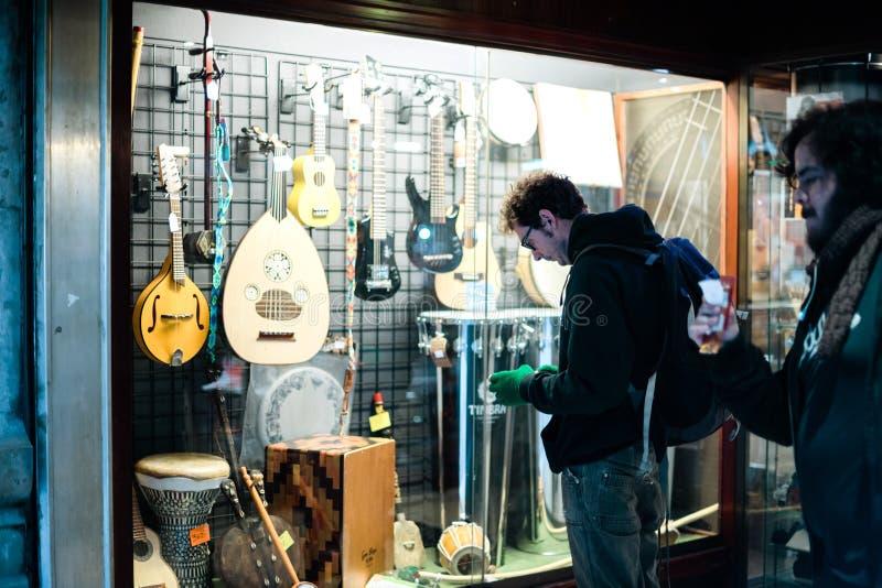 Ventana del escaparate de la tienda musical que ofrece los instrumentos musicales diversos imagenes de archivo