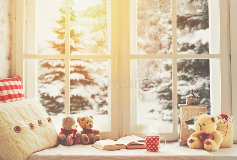 Ventana del invierno de la Navidad con un libro, una taza de té caliente fotos de archivo libres de regalías