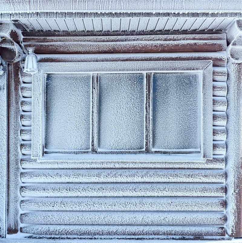 Ventana del invierno, descensos del agua y copos de nieve en un cristal de ventana foto de archivo
