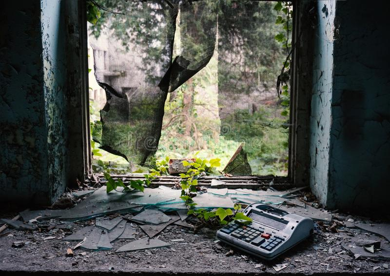 Ventana destruida en el edificio abandonado con la hiedra y una caja registradora quebrada fotos de archivo