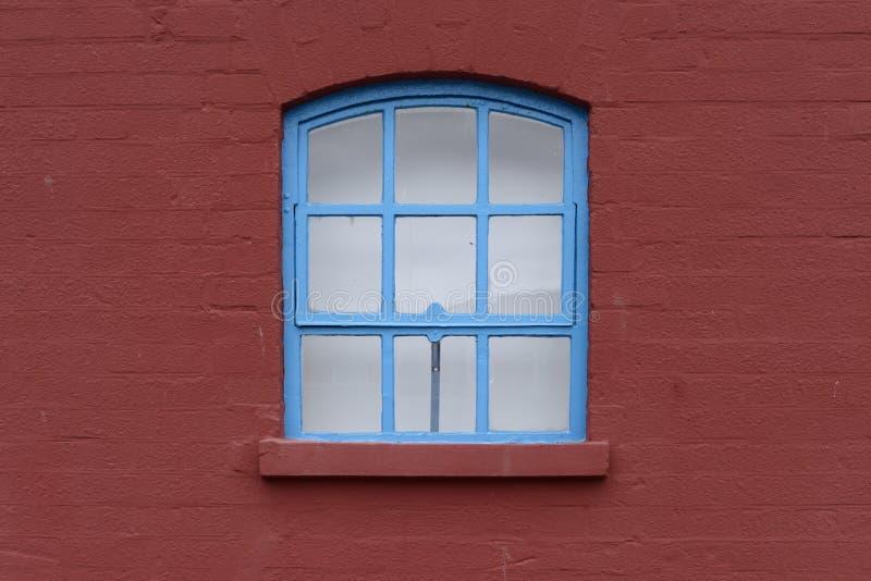 Ventana enmarcada azul con el arco en una pared de ladrillo fotografía de archivo libre de regalías