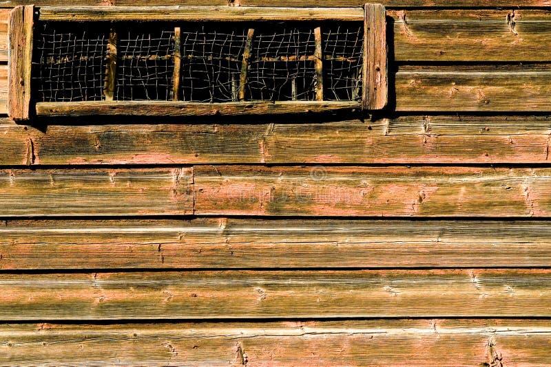 Ventana estrecha con una malla de alambre en una pared lamentable marrón clara de un granero viejo, Porvoo, Finlandia fotos de archivo libres de regalías