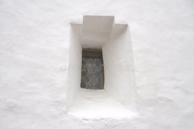 Ventana estrecha en la pared de piedra blanca imagen de archivo libre de regalías