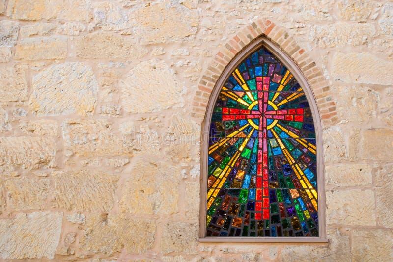 Ventana gótica de la iglesia del estilo con la Cruz Roja del vidrio manchado hecha del vitral imagen de archivo libre de regalías
