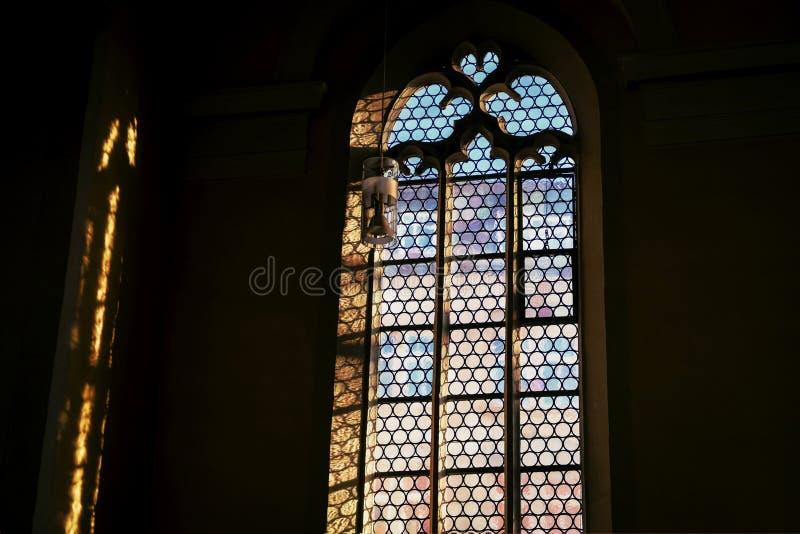 Ventana hermosa y una lámpara en la iglesia católica alemana Luz y sombra imagenes de archivo
