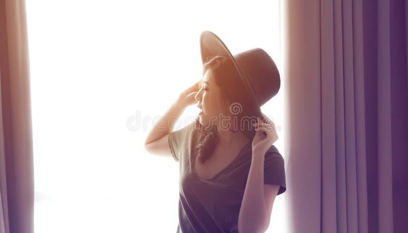 Ventana larga de la luz de la cortina del hogar del sombrero del desgaste del pelo de la mujer asiática de la raza mixta foto de archivo libre de regalías