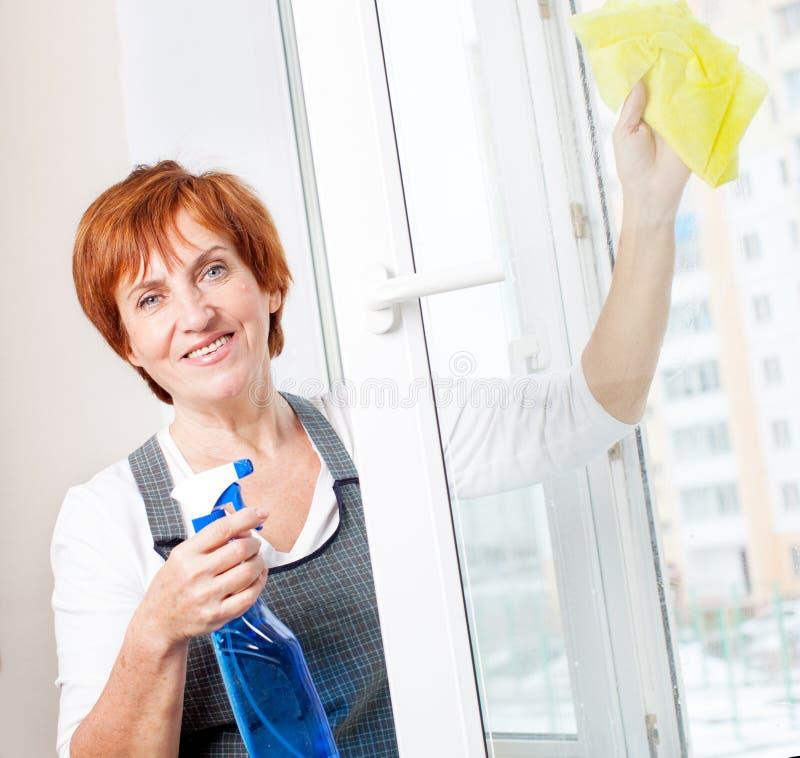 Ventana madura de la limpieza de la mujer foto de archivo libre de regalías