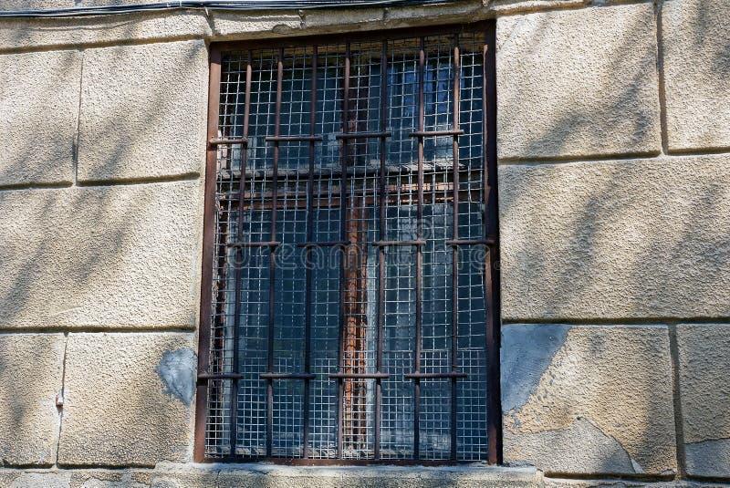 Ventana marrón vieja detrás de barras en un muro de cemento gris imagen de archivo