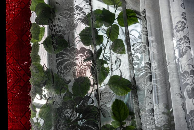 Ventana ordinaria casera con Tulle blanca transparente y las cortinas rojas del sat?n D?a brillante soleado, invierno afuera En l fotografía de archivo