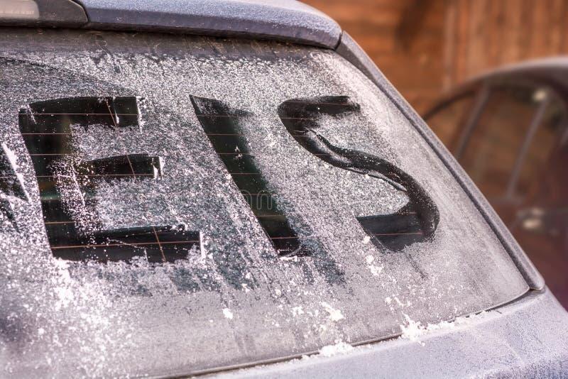 Ventana posterior helada de un coche con la palabra alemana para el hielo imagen de archivo