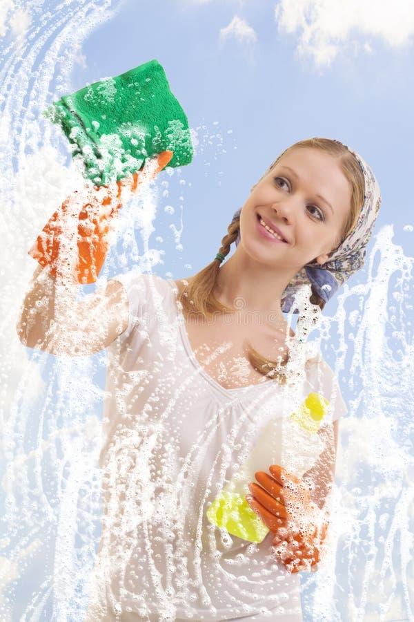 Ventana que se lava de la mujer joven foto de archivo libre de regalías