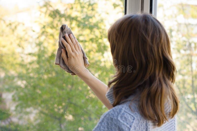 Ventana que se lava de la mujer joven foto de archivo
