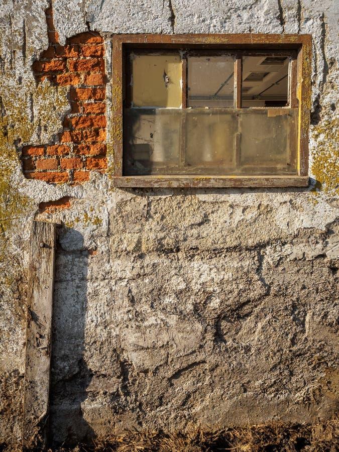 Ventana sucia vieja del granero y pared dañada foto de archivo