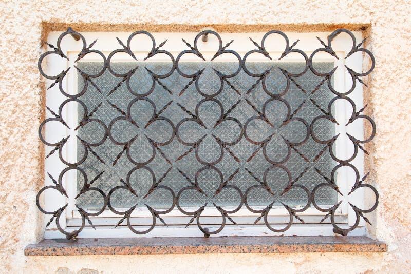 Ventana vieja con las rejas decorativas del hierro con los detalles decorativos imagen de archivo