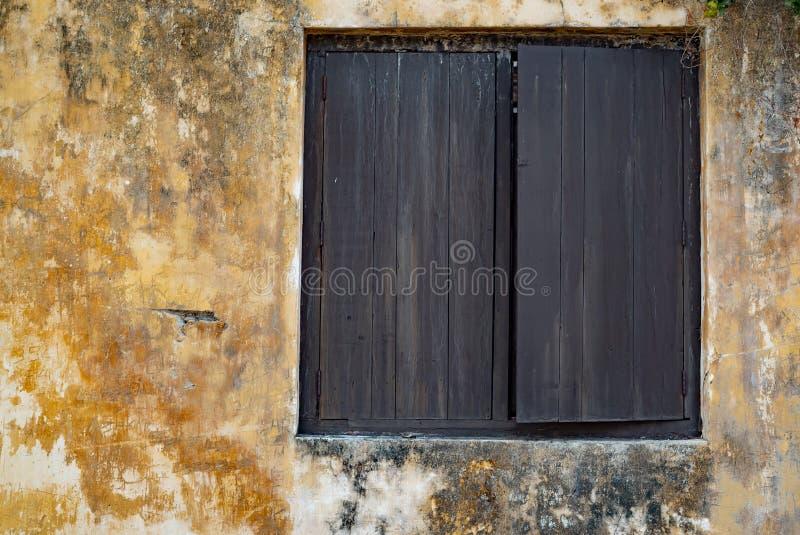 Ventana vieja con los obturadores de madera en la pared del estuco y el espacio amarillos de la copia fotografía de archivo