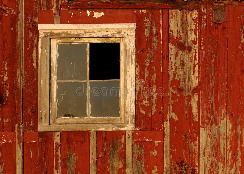 Ventana vieja del granero en la pared roja imagenes de archivo