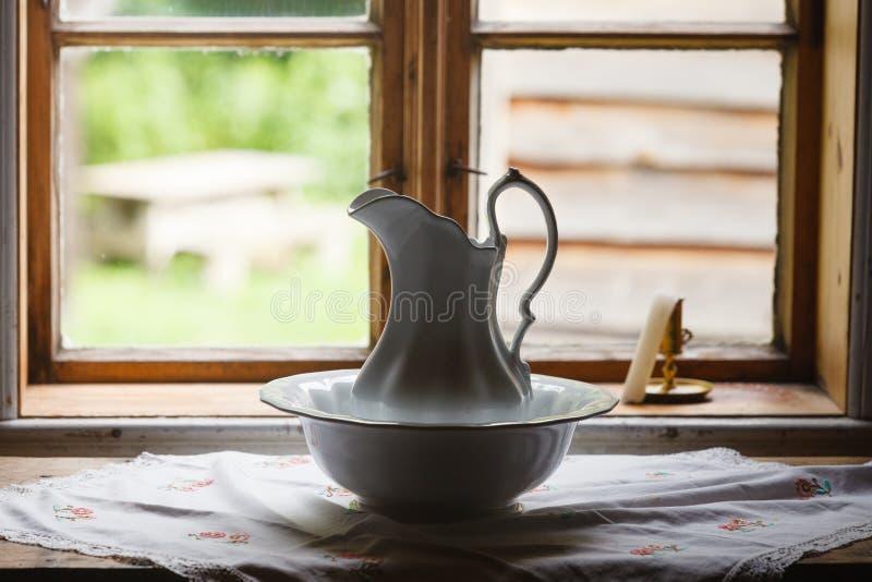 Ventana vieja del vintage, jarro de cerámica en primero plano imagenes de archivo