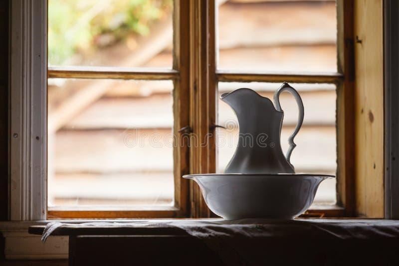 Ventana vieja del vintage, jarro de cerámica en primero plano imágenes de archivo libres de regalías