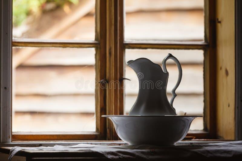 Ventana vieja del vintage, jarro de cerámica en primero plano fotografía de archivo libre de regalías