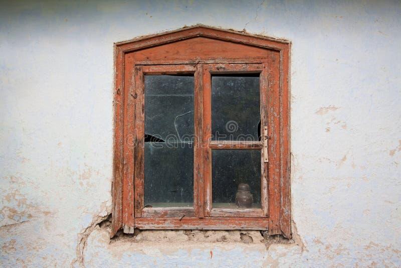 Ventana vieja y destruida con el marco de madera y vidrio quebrado, detalle de una casa de campo solitaria abandonada imagen de archivo