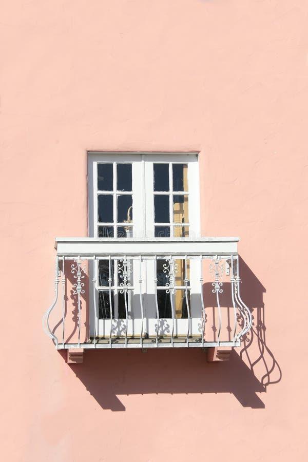 Ventana y balcón en la pared rosada fotos de archivo libres de regalías