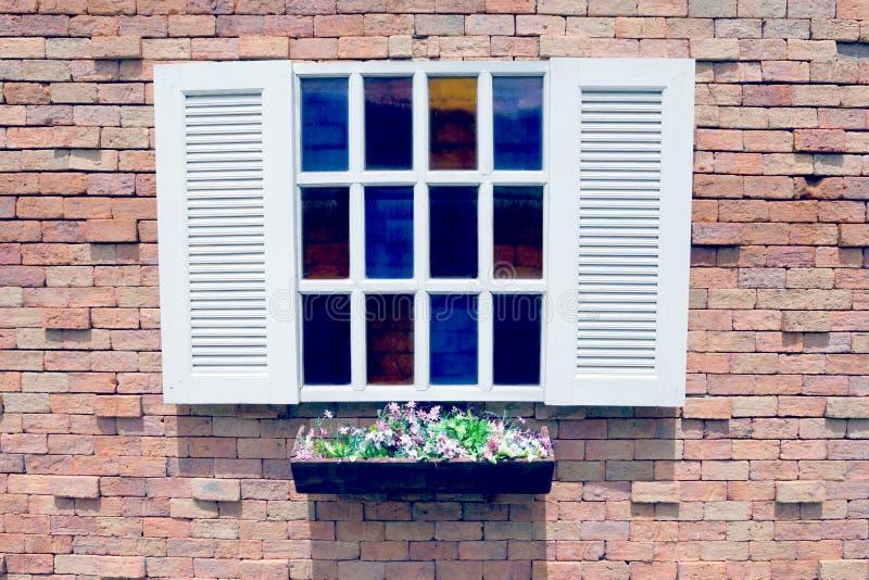 Ventana y maceta de madera blancas en el fondo de la pared de ladrillo, efecto del filtro foto de archivo libre de regalías