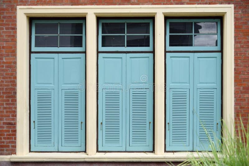Ventanas azules claras de la combinación en la pared de ladrillo fotos de archivo