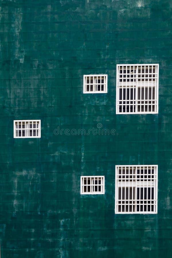 Ventanas blancas contra la pared verde imagenes de archivo