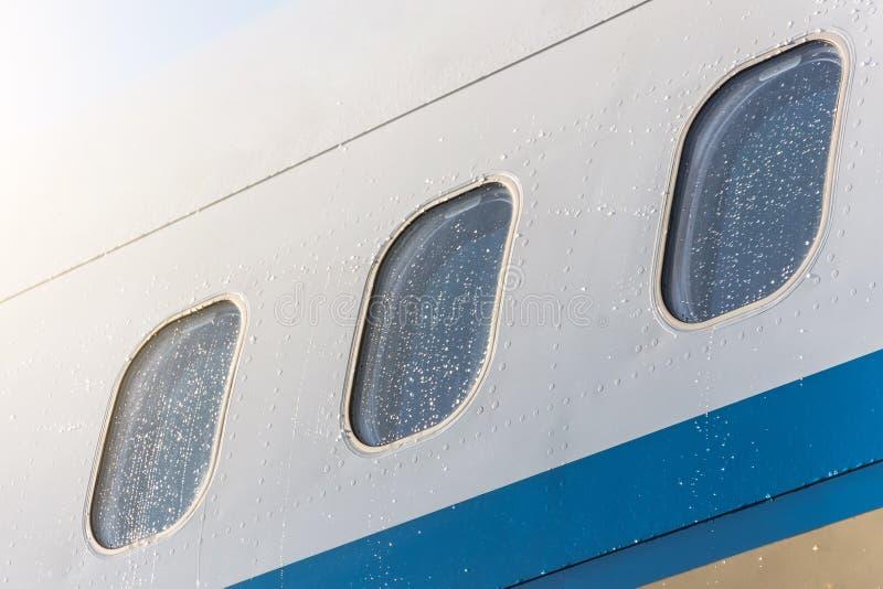 Ventanas de la porta de un tiempo lluvioso del aeroplano en gotas de lluvia del agua, primer fotos de archivo libres de regalías