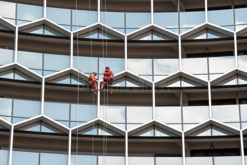 Ventanas industriales de un edificio alto, limpieza del lavado del personal de los trabajadores del alpinismo del hombre que limp imagen de archivo
