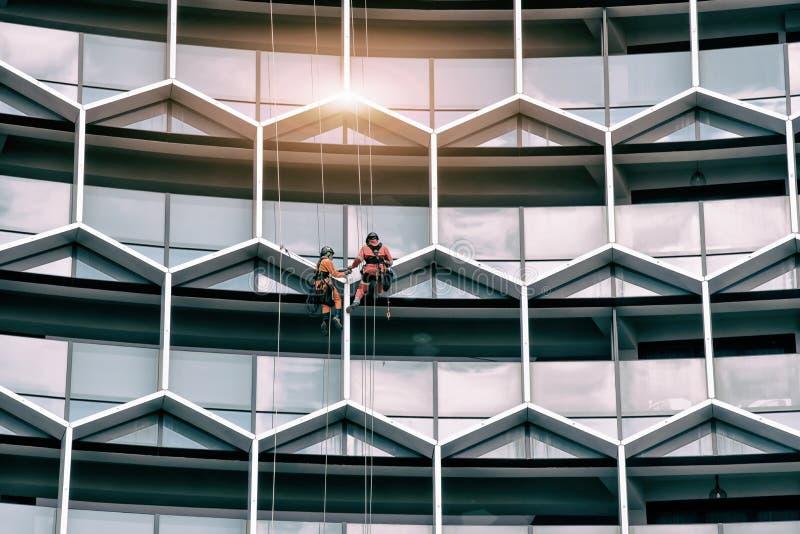 Ventanas industriales de un edificio alto, limpieza del lavado del personal de los trabajadores del alpinismo del hombre que limp foto de archivo libre de regalías