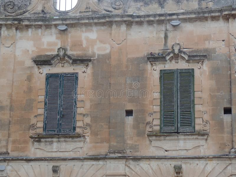 Ventanas italianas tradicionales con los obturadores en Lecce, Puglia, Italia meridional foto de archivo libre de regalías