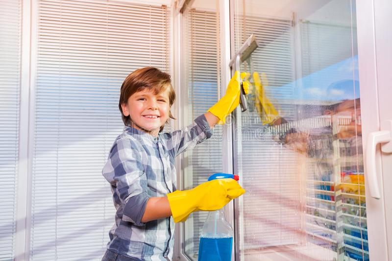 Ventanas que se lavan sonrientes del muchacho con el limpiador de ventana imagenes de archivo