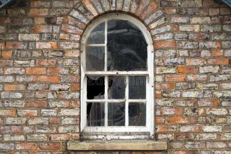 Ventanas quebradas en una casa dilapidada fotografía de archivo