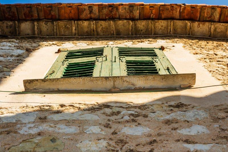 Ventanas shuttered verdes contra una pared marrón resistida en Eze, Francia fotografía de archivo libre de regalías