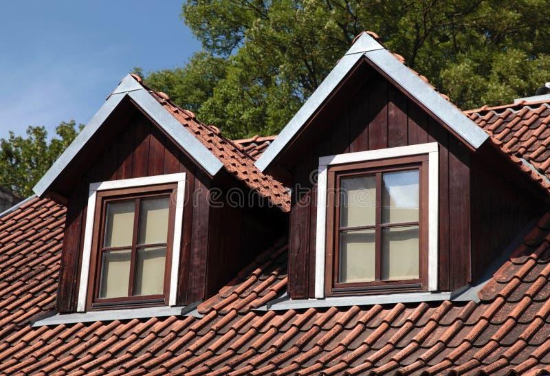 Ventanas tejadas anaranjadas del tejado y de la buhardilla en casa vieja foto de archivo - Ventanas de buhardilla ...