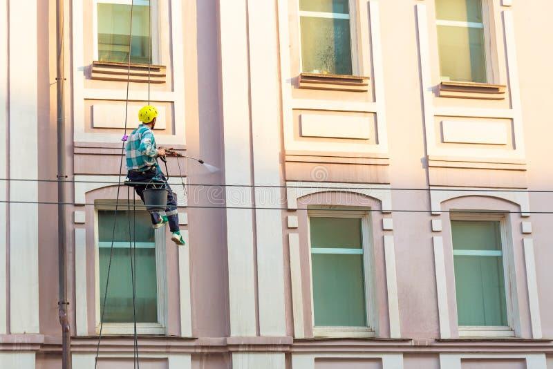 Ventanas y pared de la limpieza del hombre en la ciudad vieja bulding fotografía de archivo