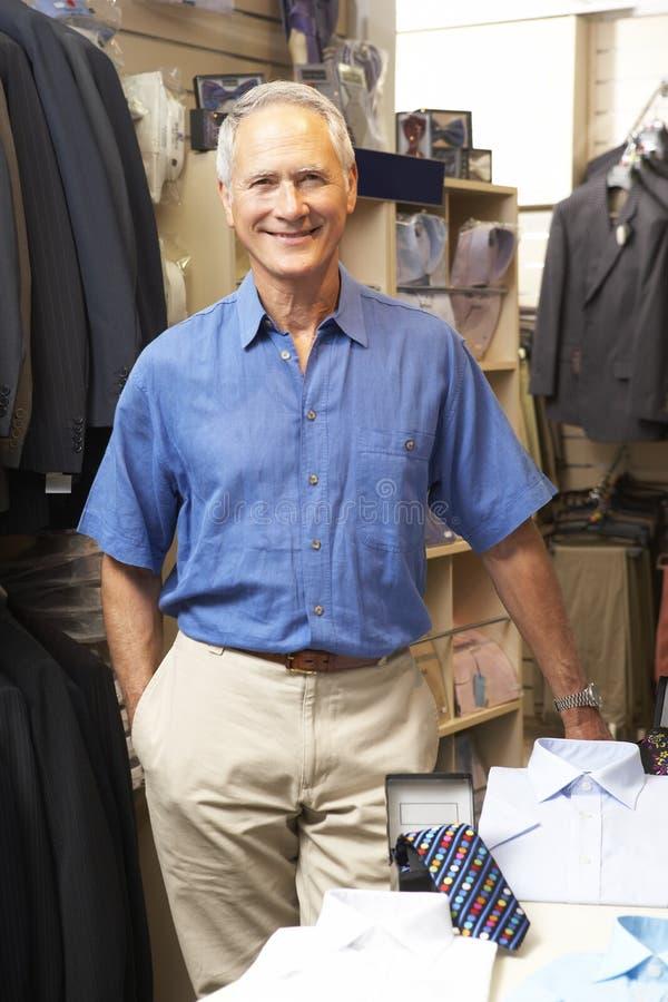Ventas masculinas auxiliares en almacén de ropa fotos de archivo libres de regalías
