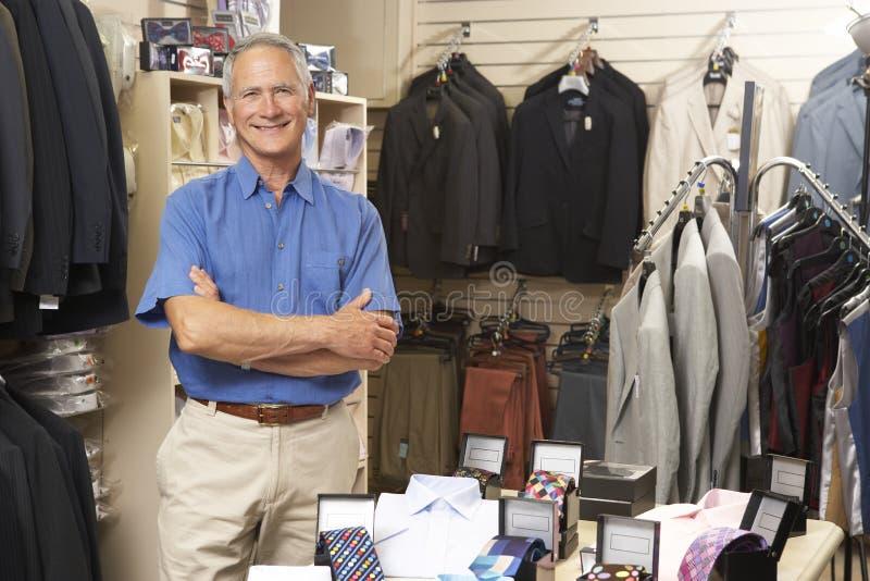 Ventas masculinas auxiliares en almacén de ropa imágenes de archivo libres de regalías