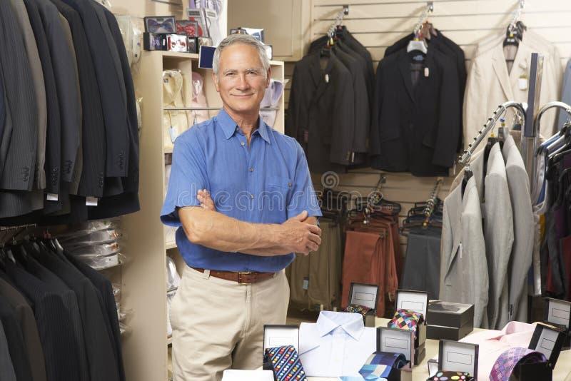 Ventas masculinas auxiliares en almacén de ropa fotos de archivo