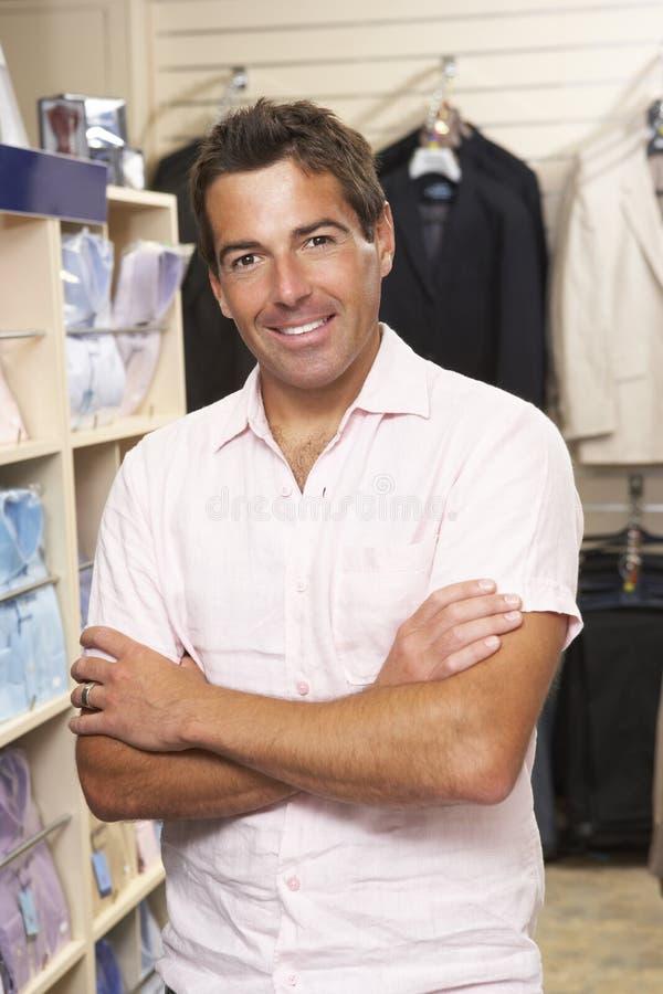 Ventas masculinas auxiliares en almacén de ropa imagen de archivo