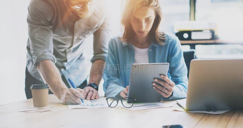 Ventas Team Working Modern Office de la foto Mujer que usa el ordenador portátil genérico del diseño, hombre que sostiene el lápi foto de archivo