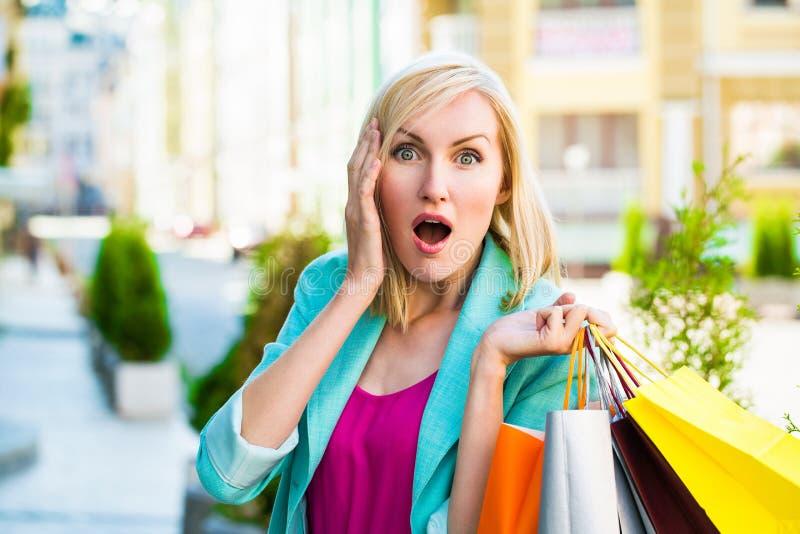 Vente, achats, tourisme et concept heureux de personnes - belle femme avec des paniers dans le ctiy photos stock