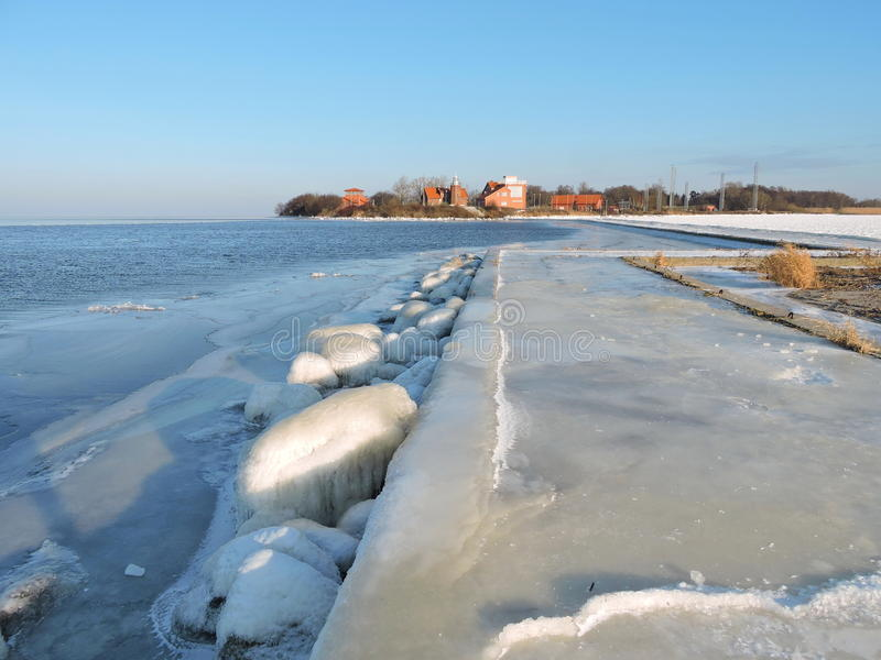 Vente Cape in winter , Lithuania. Old Vente Lighthouse and pear in ice in winter, Lithuania stock photos